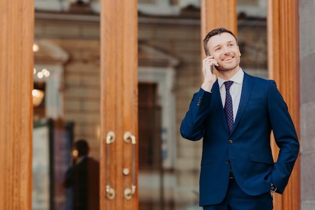 Gli uomini parlano al telefono per strada, vestiti con un abito formale, tengono le mani in tasca Foto Premium