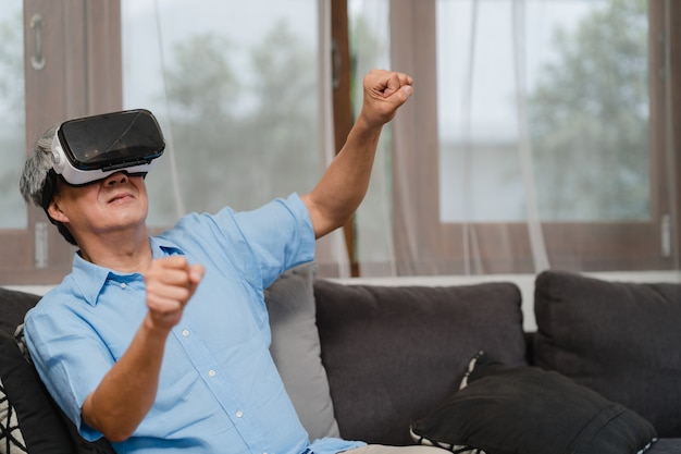 Gli uomini senior asiatici giocano a casa. divertimento felice maschio cinese senior senior asiatico e realtà virtuale, vr che gioca mentre sofà di menzogne nel concetto del salone a casa. Foto Gratuite