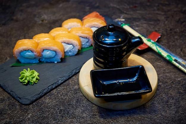Gli utensili neri per la salsa di soia su un bordo di legno rotondo contro un fondo dei rotoli di sushi su un bordo di pietra Foto Premium