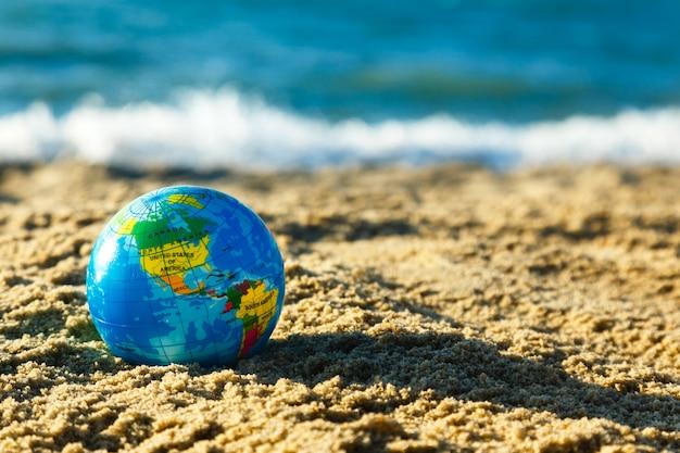 Globo del pianeta terra su una spiaggia di sabbia su uno sfondo di oceano. Foto Premium