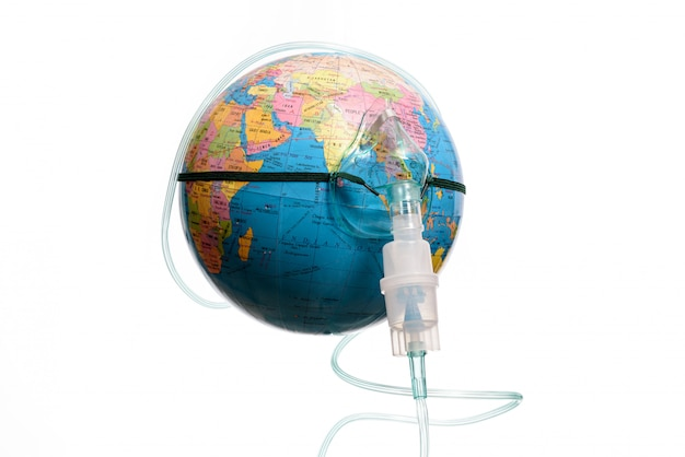 Globo terrestre con una maschera per inalatore, isolato su uno sfondo bianco. pericolo di epidemia umana. Foto Premium