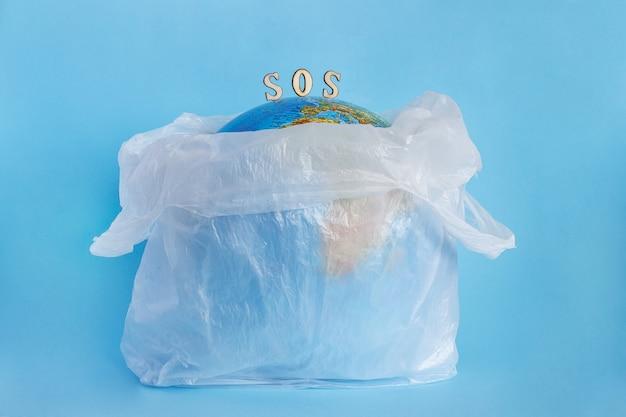 Globo terrestre in sacchetto di plastica e iscrizione sos, sfondo blu. concetto Foto Premium