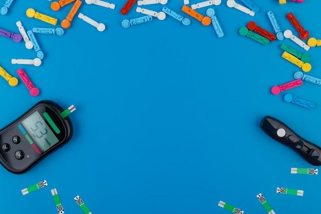 Glucometro. un dispositivo per misurare i livelli di zucchero nel sangue. strisce reattive, pillole su sfondo blu. Foto Premium