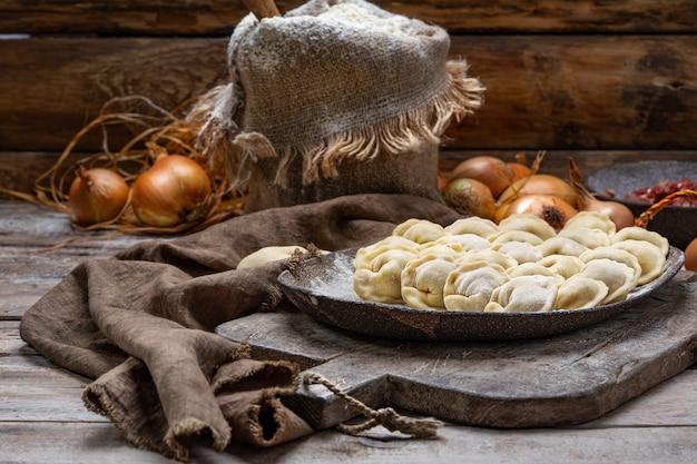 Gnocchi crudi della carne - pelmeni russo sul tagliere e sugli ingredienti Foto Premium