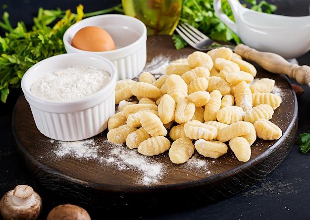 Gnocchi fatti in casa non cotti con salsa di funghi e prezzemolo Foto Premium