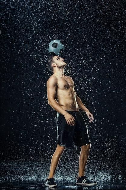 Gocce d'acqua intorno al calciatore Foto Gratuite