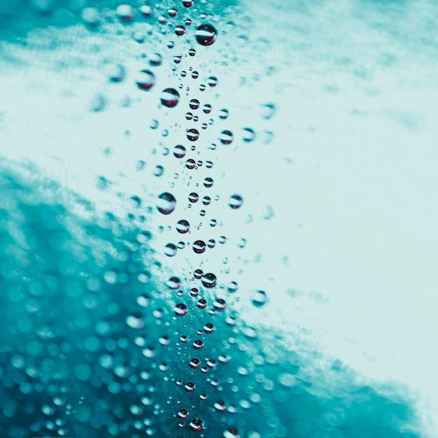 Gocce di acqua astratte su sfondo di vetro turchese Foto Gratuite