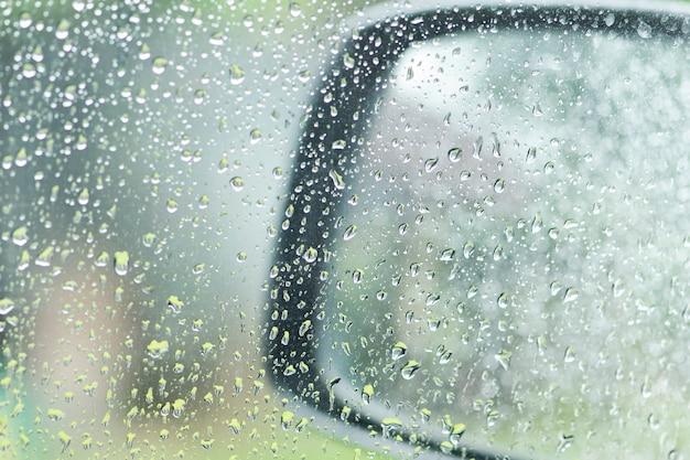 Gocce di pioggia sul finestrino e sullo specchietto auto in una giornata piovosa Foto Premium