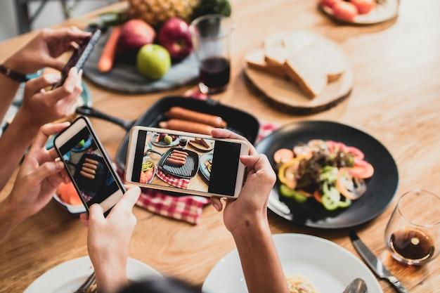 Goditi la cena mangiando festa e festeggiando con gli amici e scattando foto per telefono Foto Premium