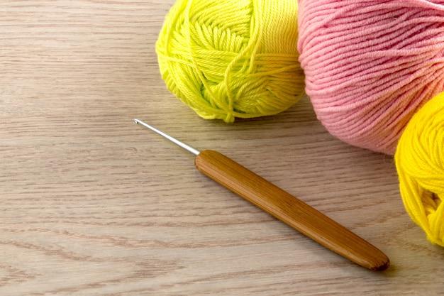 Gomitoli di lana, ferri da maglia, sul tavolo di legno Foto Premium