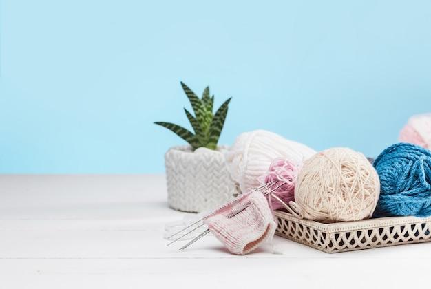 Gomitoli di lana su fondo di legno bianco Foto Gratuite
