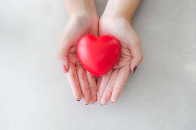 Gomma a forma di cuore rosso sulla bella mano di donna Foto Premium
