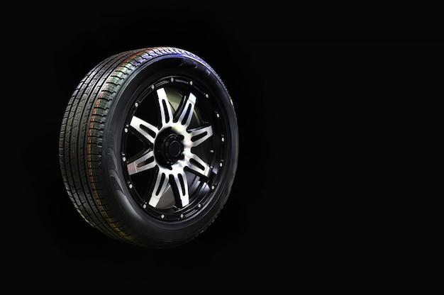 Gomma della ruota di automobile con l'orlo della lega isolato su fondo nero, spazio della copia Foto Premium