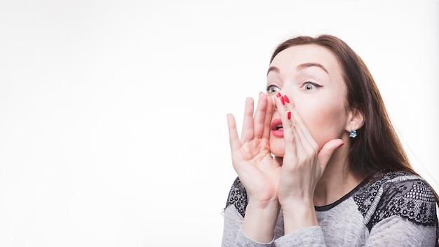 Gossip di sussurro della giovane donna contro fondo bianco Foto Gratuite