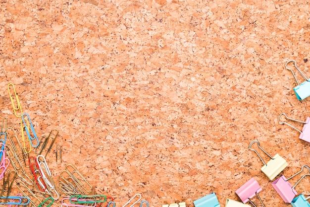 Graffette multicolori e clip di raccoglitore sparse su sfondo di sughero Foto Gratuite
