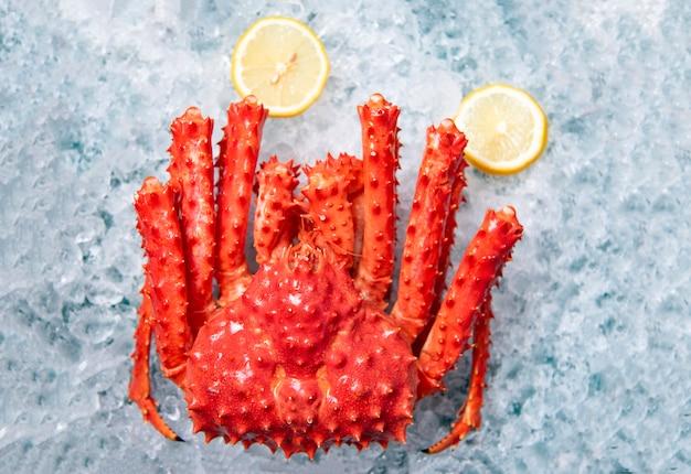 Granchio reale d'alasca su ghiaccio con la vista superiore del fondo del limone - hokkaido rosso del granchio al mercato dei frutti di mare Foto Premium