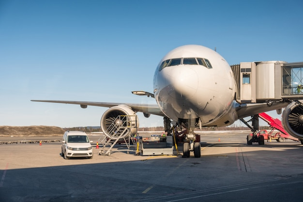 Grande aereo passeggeri parcheggiato su pista con collegare corridoi Foto Premium