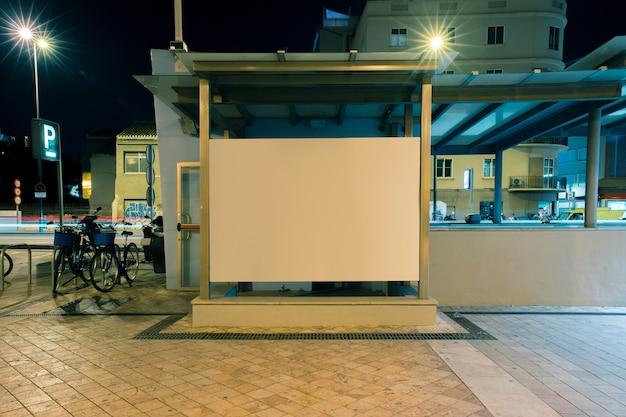 Grande cartellone bianco su un muro strada di notte Foto Gratuite