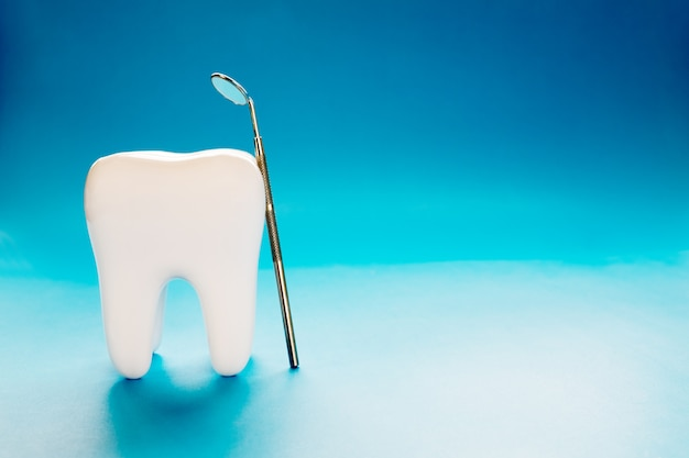 Grande dente e strumento dentista su sfondo blu. Foto Premium