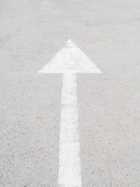 Grande freccia bianca su asfalto Foto Gratuite