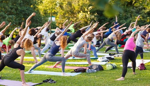 Grande gruppo di adulti che frequentano una lezione di yoga fuori nel parco Foto Premium