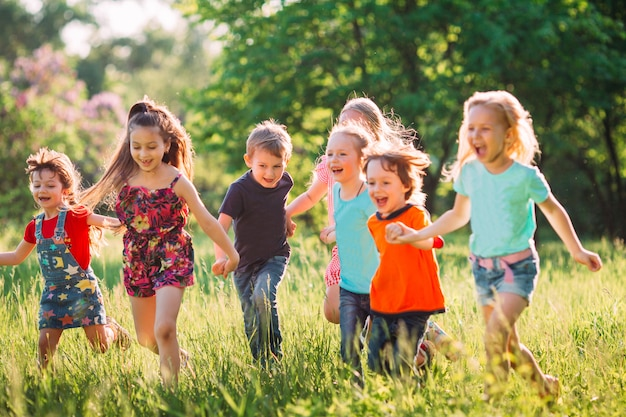 Grande gruppo di bambini, amici ragazzi e ragazze che corrono nel parco sulla soleggiata giornata estiva in abiti casual. Foto Premium