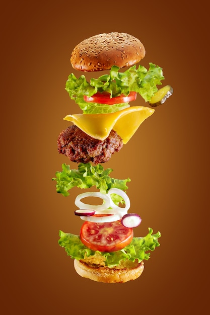 Grande gustoso hamburger fatto in casa con ingredienti volanti su sfondo bianco. isolato. Foto Premium