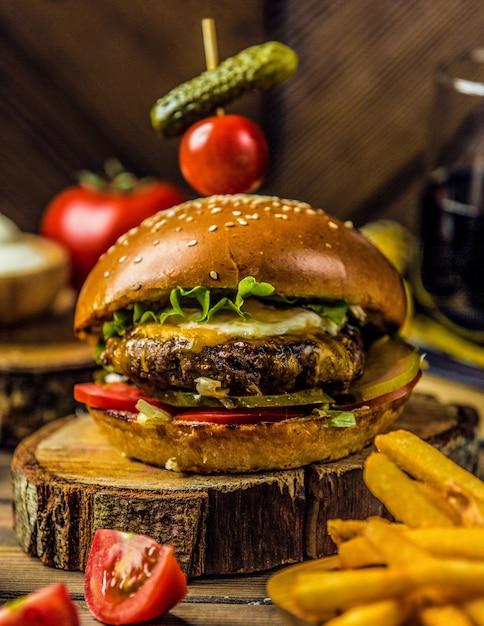 Grande hamburger max in piedi su un pezzo di legno Foto Gratuite