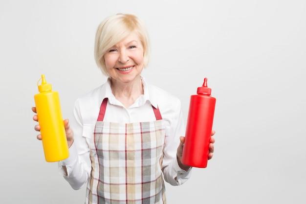 Grande immagine dell'anziana che tiene in mano due bottiglie di sauses. vuole cucinare del cibo gustoso per la sua amata. Foto Premium