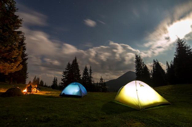 Grande luna luminosa in cielo nuvoloso blu scuro sopra due tende turistiche sulla foresta erbosa verde. Foto Premium