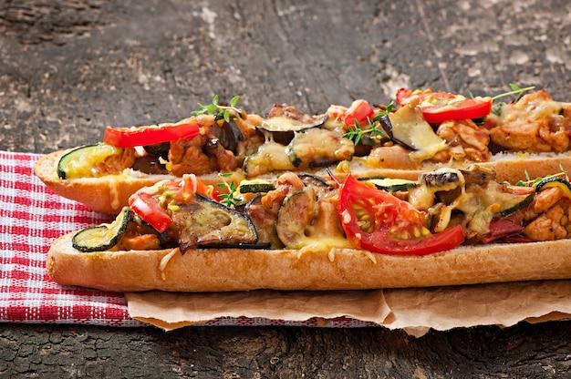 Grande panino con verdure arrosto (zucchine, melanzane, pomodori) con formaggio e timo su fondo in legno vecchio Foto Gratuite