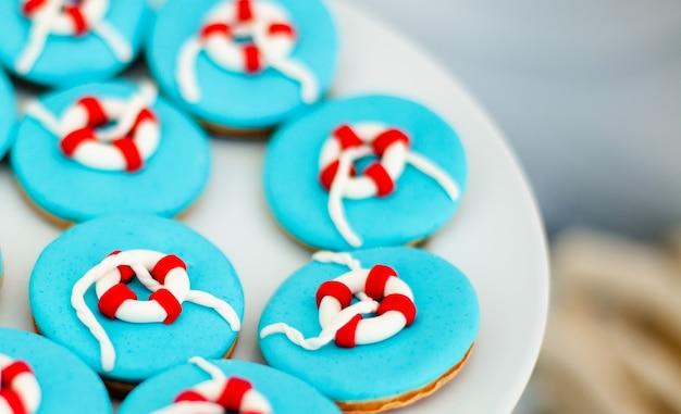 Grande piatto bianco con molti biscotti di pane allo zenzero con glassa blu brillante Foto Premium