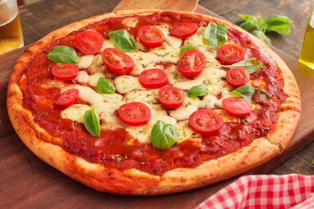 Grande pizza margherita sul tagliere di legno Foto Gratuite
