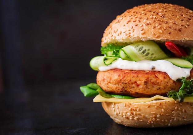 Grande sandwich - hamburger con succosa hamburger di pollo, formaggio, cetriolo, peperoncino e tartaro su sfondo nero Foto Premium
