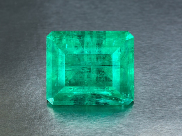 Grande smeraldo naturale su un fondo grigio, fine di percorso di ritaglio inclusa alto vicino. Foto Premium