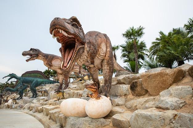 Grande statua marrone del dinosauro sulla roccia nel parco asia tailandia Foto Premium