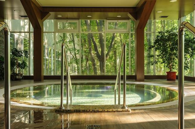 Grande vasca idromassaggio circolare nel centro benessere, la mattina presto Foto Premium