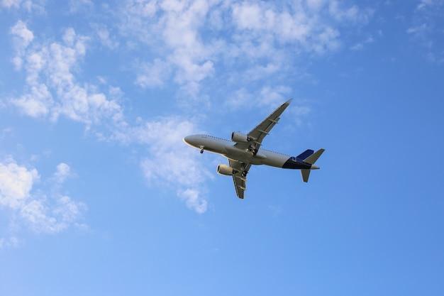 Grande volo bianco dell'aeroplano nello skyplane blu con le nuvole bianche. Foto Premium