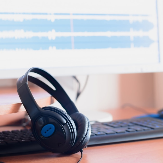 Grandi cuffie nere giacciono sul tavolo di legno del sound designer Foto Premium