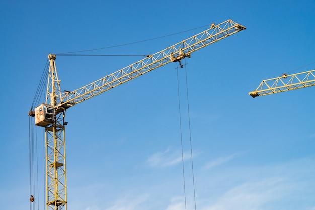 Grandi gru a torre contro il cielo blu. immagine di sfondo del primo piano dell'attrezzatura per l'edilizia con lo spazio della copia. costruire della città. Foto Premium