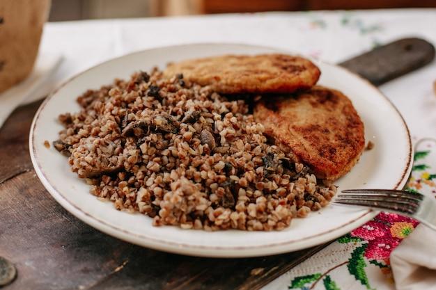 Grano saraceno cotto insieme a fette di carne fritta all'interno di pagnotte di pane piatto bianco sul tavolo colorato di tessuti durante il giorno Foto Gratuite