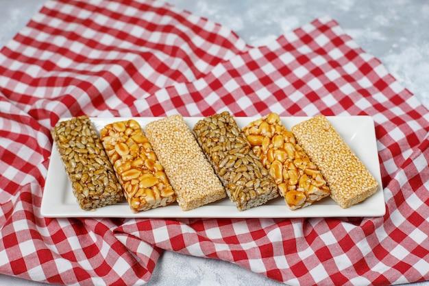 Granola bar. spuntino dolce dessert sano. sesamo, arachidi, girasole nel miele. gozinaki è cibo nazionale georgiano, dolce orientale. vista dall'alto su cemento Foto Gratuite
