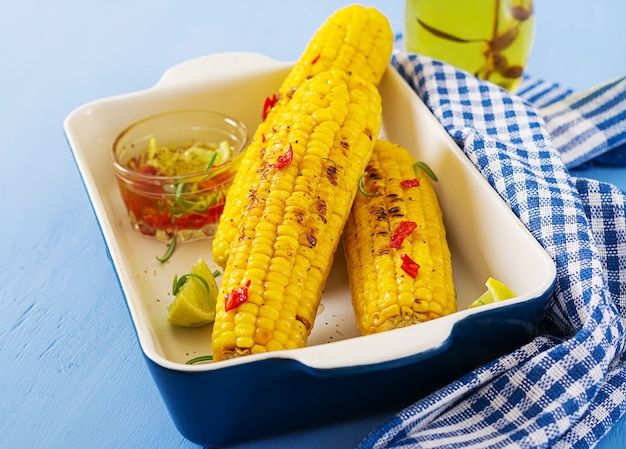 Granturco dolce alla griglia con salsa messicana, peperoncino e lime su sfondo blu. Foto Premium