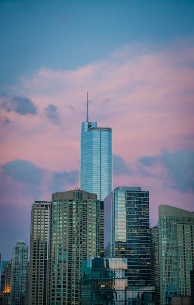 Grattacielo alto della costruzione di affari in chicago, stati uniti, con le belle nuvole rosa nel cielo blu Foto Gratuite