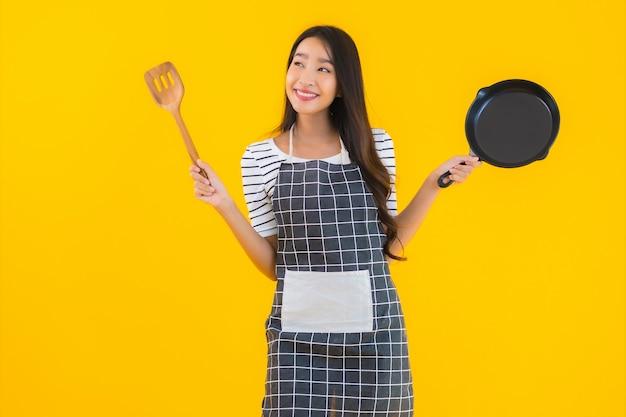 Grembiule asiatico giovane bello di usura della donna del ritratto con la pentola e la spatola nere Foto Gratuite