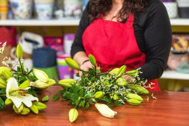 Grembiule d'uso del fiorista della donna che sta al contatore che fa mazzo per il cliente al negozio di fiore. Foto Premium