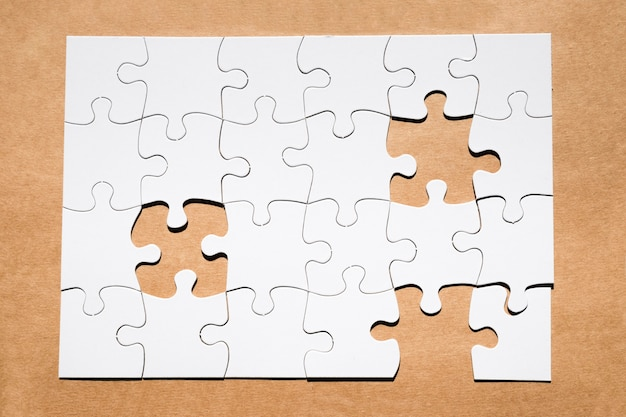 Griglia bianca di puzzle con il pezzo mancante di puzzle su carta marrone strutturata Foto Gratuite