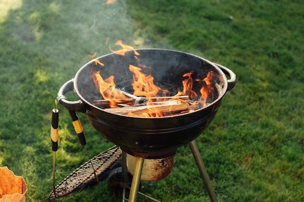 Griglia del barbecue con fuoco su erba al parco Foto Gratuite