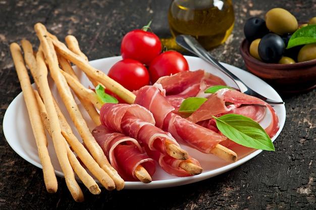 Grissini con prosciutto, olive, basilico su legno vecchio Foto Gratuite