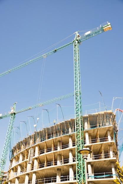 Gru a torre che costruiscono edificio residenziale Foto Gratuite